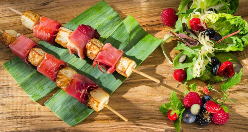 Skewers of tomino cheese wrapped in speck and celeriac, mix of lettuce leaves and soft fruits