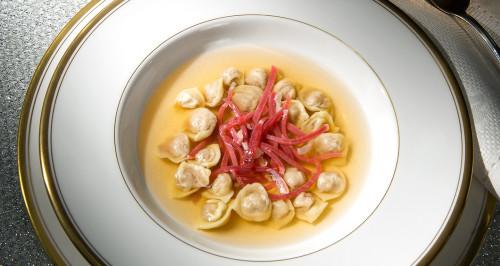 Tortellini ripieni di prosciutto crudo di parma e lonza di maiale su brodo tiepido di parmigiano