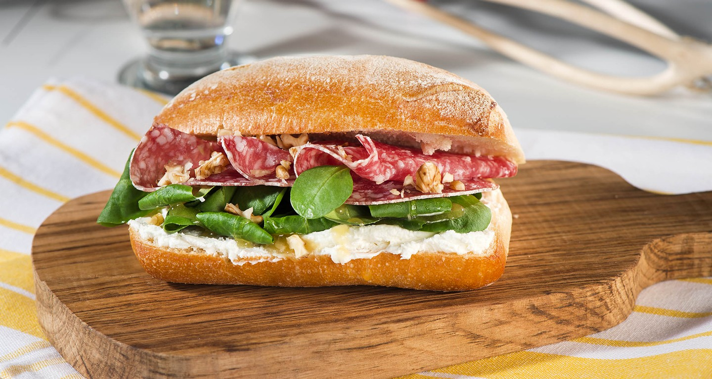 Sandwich with salami, robiola cheese, honey, soncino salad and nuts