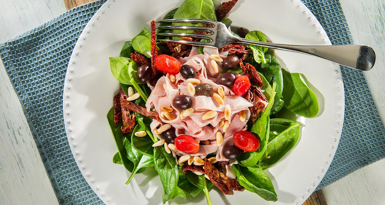 Insalata di spinacino novello, straccetti di prosciutto cotto, pinoli tostati, olive taggiasche e pomodori essiccati al sole.