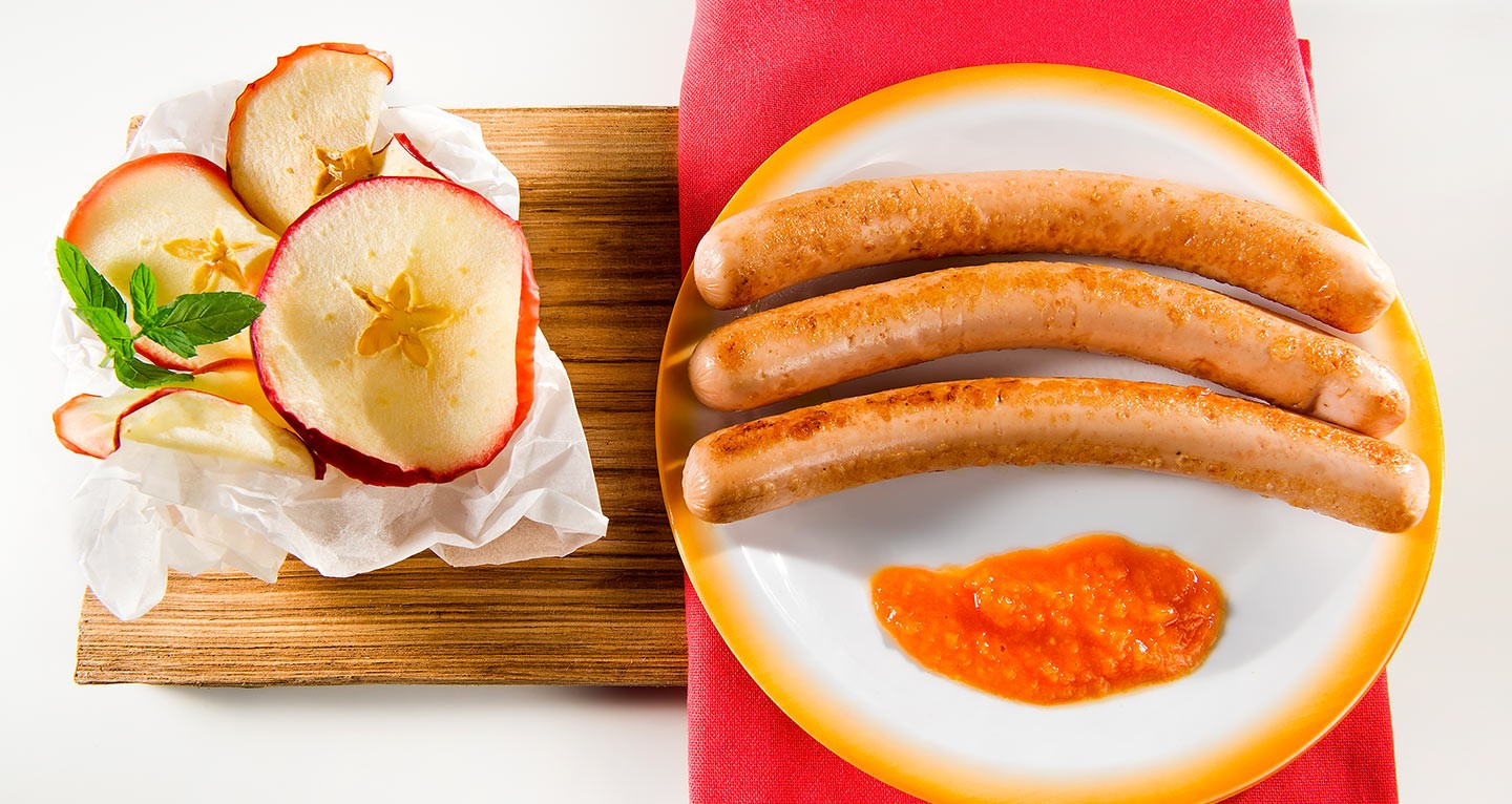 Chicken frankfurters with sweet and sour sauce and red apple chips