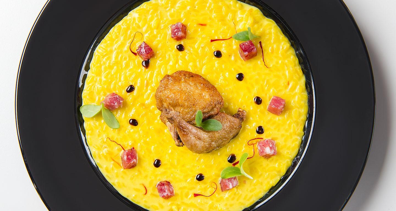 Risotto alla milanese mantecato con cubetti di salame, quaglia arrosto e aceto balsamico di Modena